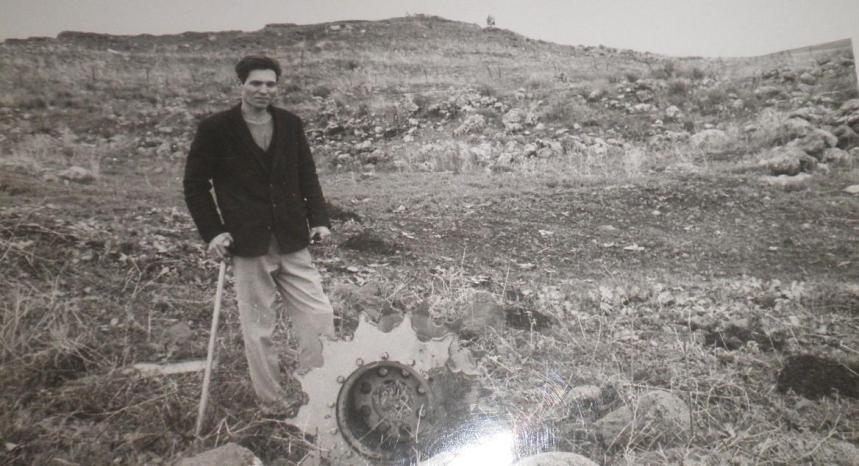 חודשיים אחרי המלחמה. עזרא ברוש חוזר לתל פאחר ליד הגל המניע של הטנק שלו (להגדלה לחצו)