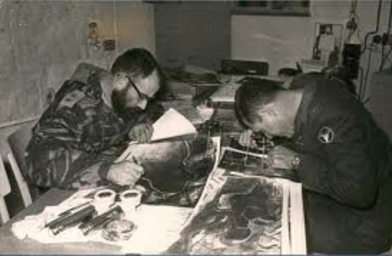 """גנדלר (משמאל) בעבודה. מפענחים תצ""""א, עוקבים אחרי כתמים שחורים שבלעו קרני שמש ומסמנים שדות מוקשים. צילום: מתוך אוסף מל""""מ"""