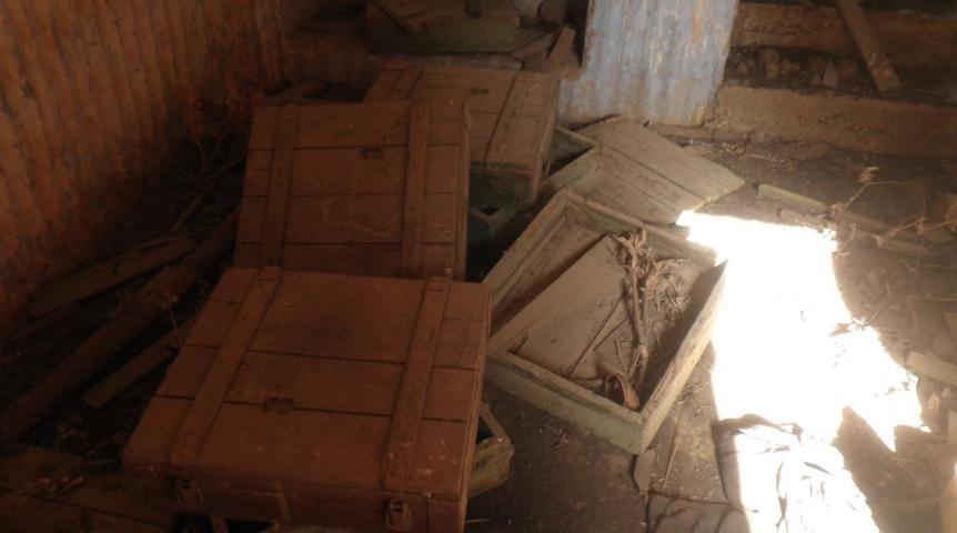ארגזי פעולה רבים, חלקם סגורים, רובצים על רצפת הבונקרים
