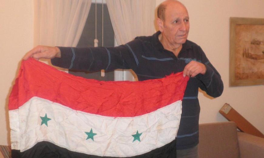 זמיר כהן בביתו בבת-ים עם דגל סוריה (מודל 1963 בעת שלטון הבעת') שהוריד מהתורן של תל פאחר בסיומו של קרב הדמים