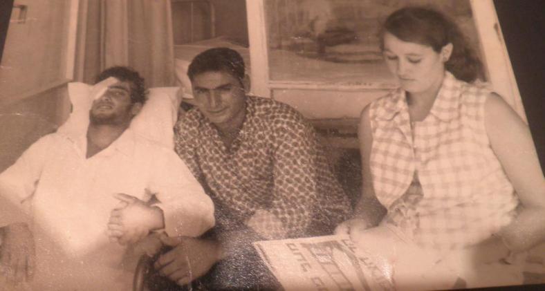 """יוני 1967, בתקופת האשפוז בבי""""ח רמב""""ם: מיכאל סייג (משמאל) אוחז בידו של אחיו, אלי. מימין: גבי שטיינר, שכנה מהמושב, מעיינת בעיתון שהכותרת שלו היא """"מעל פסגת הר הצופים"""""""
