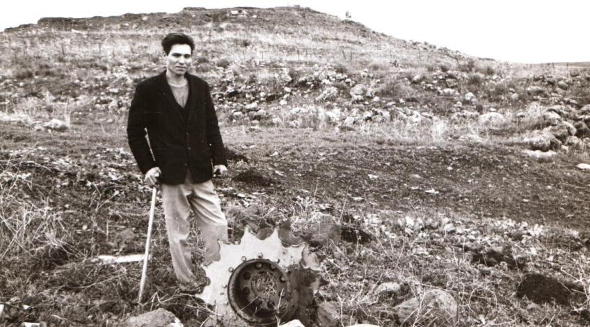 """סתיו 1967, עזרא ברוש חוזר לתל פאחר כדי לשחזר בפני צוות תורת חש""""ן את סיפור הקרב. כאן ליד הגלגל מניע של הטנק שנותר בשטח עד היום (צילום ...)"""