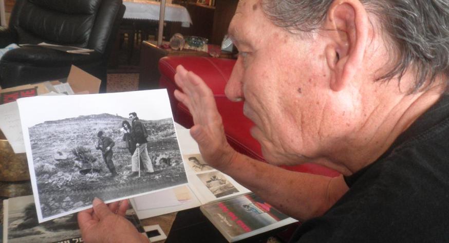 """עזרא ברוש מחזיק צילום שבו תוחקר ע""""י צוות תורת חש""""ן בסתיו 1967. לשם כך הוסע במיוחד מבית החולים לתל פאחר"""