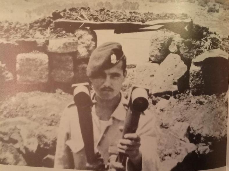 חייל סורי עם פריסקופ. בספר נכתב שהצילום הוא ממוצב מעל להבות הבשן