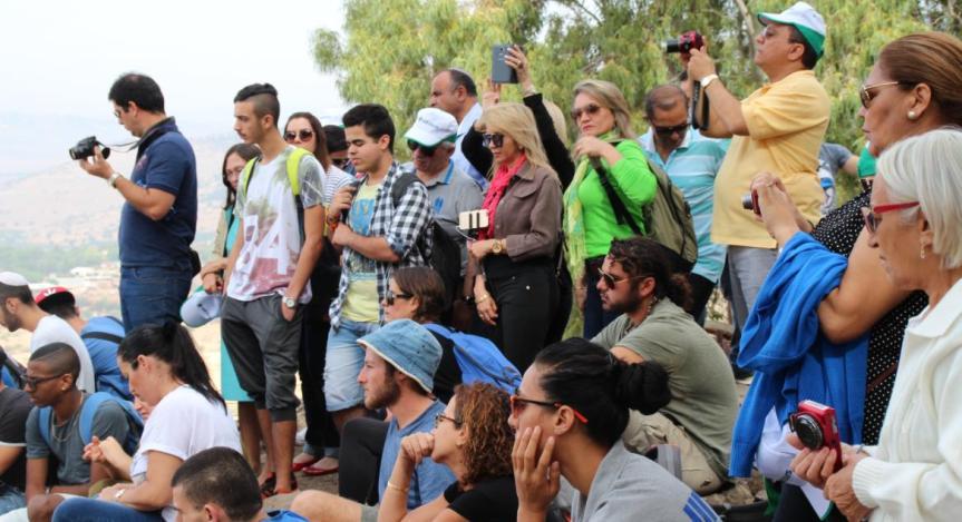 תלמידים ומורים מקשיבים לתיאור קרב תל פאחר מפי קצין חטיבת גולני