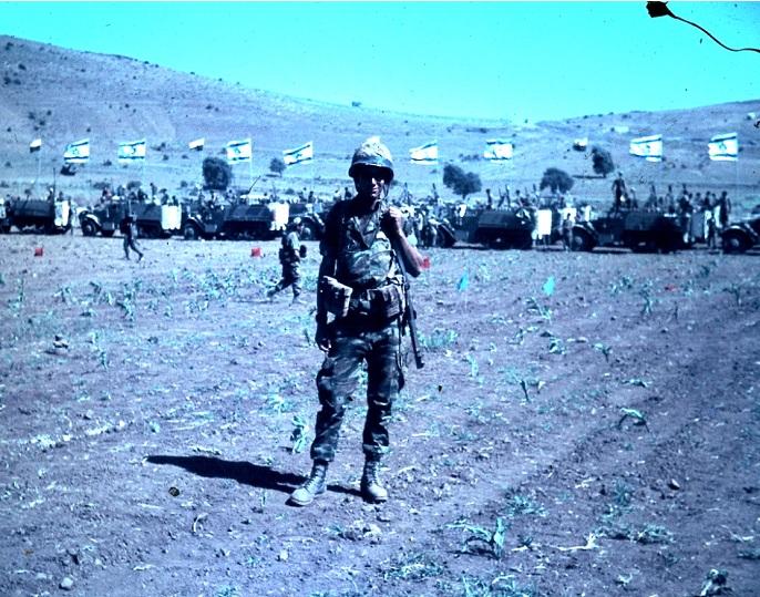 """הכותב בטכס הניצחון ברקע ניתן להבחין בזחל""""מים, כנראה של גדוד 12 ומאחוריהם קני מרגמה של גדוד המרגמות של """"גולני"""""""
