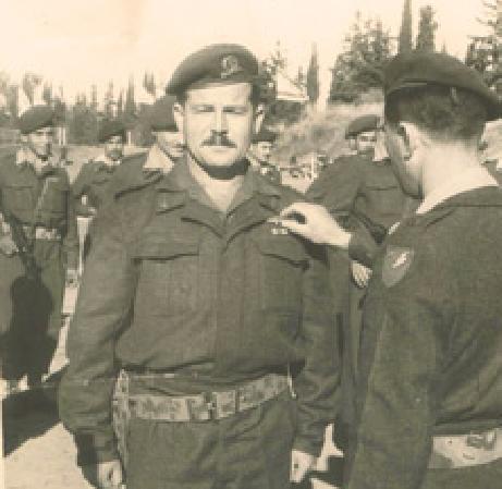 """סרן בירו ב-1957 בעת הענקת רקע אדום לכנפי הצניחה על הצניחה במעבר המיתלה במצע קדש. את הרקע מעניק לו המג""""ד רפאל איתן"""