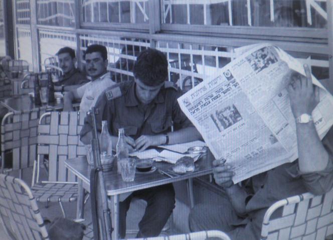 """מדינה של רדיו ועיתונים. חיילים בבית קפה עם ידיעות אחרונות. שימו לב לשמשות המודבקות בנייר דבק נגד הדף [צילום: ארכיון צה""""ל]"""